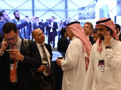 Delegates chat during the Future Investment Initiative (FII) forum at the King Abdulaziz Conference Centre in Saudi Arabia's capital Riyadh, on October 29, 2019, in front of a screen transmitting images of Saudi Crown Prince Mohammed bin Salman visiting an exhibition. - Top finance moguls and political leaders were expected …
