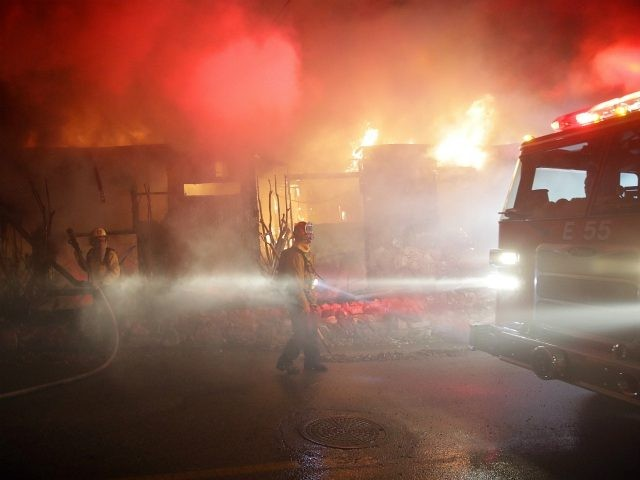 Firefighters battle the Getty fire as it burns down a home along Tigertail Road, Monday, Oct. 28, 2019, in Los Angeles. (AP Photo/Marcio Jose Sanchez)