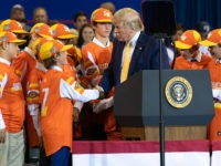 """US President Donald Trump (C) shakes hands with a member of the Little League World Championship baseball team, the Eastbank All Stars of Louisiana, during a """"Keep America Great"""" rally at Sudduth Coliseum at the Lake Charles Civic Center in Lake Charles, Louisiana, on October 11, 2019. (Photo by SAUL …"""
