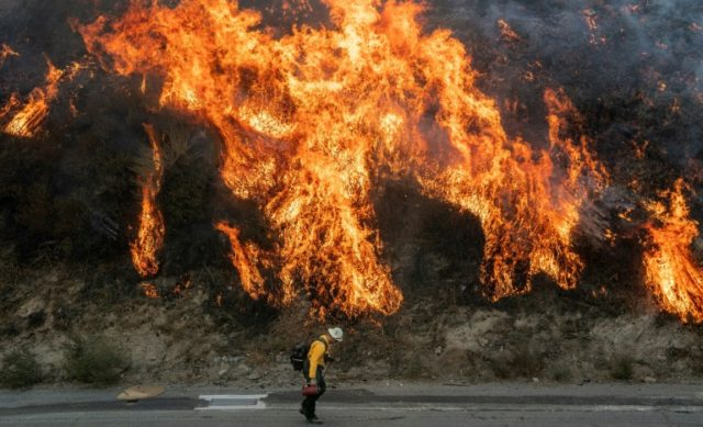A firefighter walks near flames during the Saddleridge fire in southern California
