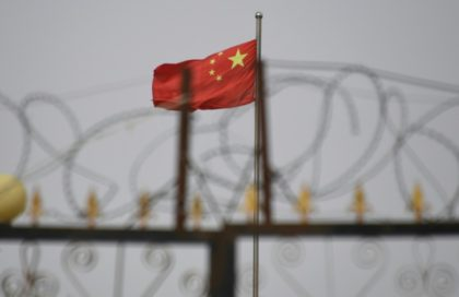 The Chinese flag flies behind razor wire at a housing compound in Yangisar, south of Kashgar, in China's western Xinjiang region