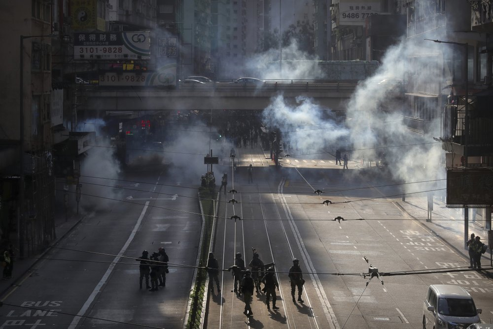 Police officers fire tear gas at demonstrators during a protest in Hong Kong, Saturday, Nov. 2, 2019. Defying a police ban, thousands of black-clad masked protesters are streaming into Hong Kong's central shopping district for another rally demanding autonomy in the Chinese territory as Beijing indicated it could tighten its grip. (AP Photo/Kin Cheung)