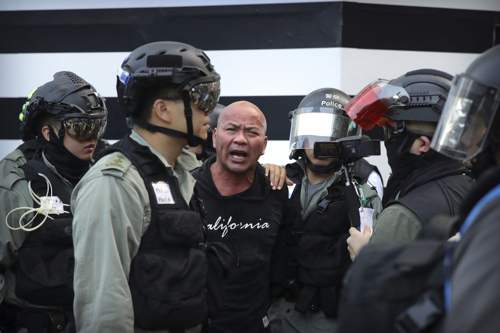 Police officers in riot gear detain a man during an anti-government protest in Hong Kong, Saturday, Nov. 2, 2019. Defying a police ban, thousands of black-clad masked protesters are streaming into Hong Kong's central shopping district for another rally demanding autonomy in the Chinese territory as Beijing indicated it could tighten its grip. (AP Photo/Kin Cheung)