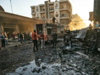 Security forces and civilians gather the site of bombings in the Syrian Kurdish-majority city of Qamishli in the northeastern Hasakah province, on November 11, 2019. - Three simultaneous bombings caused by two car bombings and an explosives-rigged motorcycle rocked a market in the Syrian city of Qamishli, killing at least …