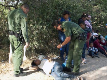 Border Patrol agents rescue a distressed migrant woman. (File Photo: U.S. Border Patrol/Barry Bahler)