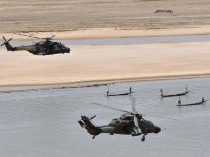 French President Emmanuel Macron flies over Gao in a military helicopter, left, as he visits the troops of Operation Barkhane, France's largest overseas military operation, in Gao, northern Mali, Friday, May 19, 2017. On his first official trip outside Europe, new French President Emmanuel Macron is highlighting his determination to …