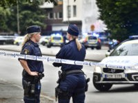 Police stand next to a cordon in central Malmo, southern Sweden, Monday, June 18, 2018. A Swedish newspaper is reporting that four people have injured in a shooting near a police station in the southern city of Malmo. Witnesses told newspaper Aftonbladet they heard what sounded like 15 to 20 …