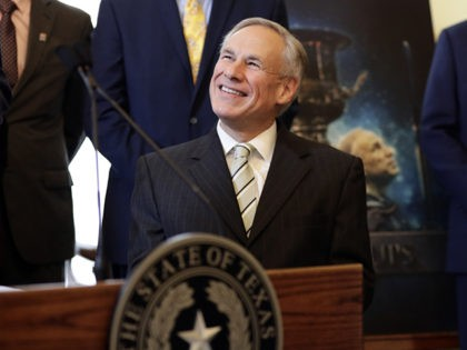 A poster with an image of Texas Gov. Greg Abbott is seen behind Abbott at a news conference where he was presented the Governor's Cup by Site Selection Magazine, Monday, March 4, 2019, in Austin, Texas. Texas won for having the most qualified projects of any state according to their …