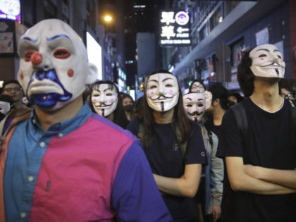 People in Guy Fawkes masks gather on a street in Hong Kong, Thursday, Oct. 31, 2019. Hong Kong authorities are bracing as pro-democracy protesters urged people on Thursday to celebrate Halloween by wearing masks on a march in defiance of a government ban on face coverings. (AP Photo/Kin Cheung)