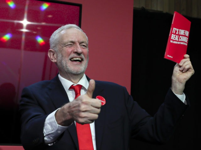 Jeremy Corbyn, Leader of Britain's opposition Labour Party, gives a thumbs up holding a copy of the manifesto on stage at the launch of Labour's General Election manifesto, at Birmingham City University, England, Thursday, Nov. 21, 2019. Britain goes to the polls on Dec. 12. (AP Photo/Kirsty Wigglesworth)
