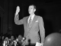 Alger Hiss, former State Department official, under accusation as aid to Communist wartime spy ring in Washington, August 25, 1948, examines record on the witness stand before the House Un-American Activities Committee; takes oath; arrives for hearing. (AP Photo)