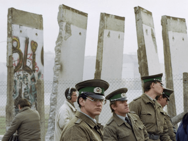 FILE - In this Nov. 13, 1989, file photo, East German border guards stand in front of segments of the Berlin Wall, which were removed to open the wall at Potsdamer Platz passage in Berlin. Months before the Berlin Wall fell on Nov. 9, 1989, with the Soviet stranglehold over …