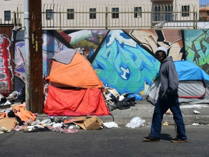 A pedestrian walks past tents and trash on a sidewalk in downtown Los Angeles on May 30, 2019. - The city of Los Angeles on May 29 agreed to allow homeless people on Skid Row to keep their property and not have it seized, providing the items are not bulky …