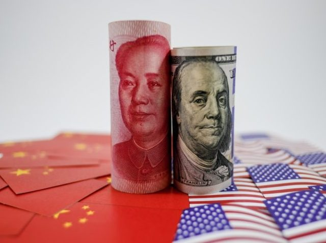 China yuan banknote on China flags and US dollar banknote on united states flags for trade war economy crisis concept.