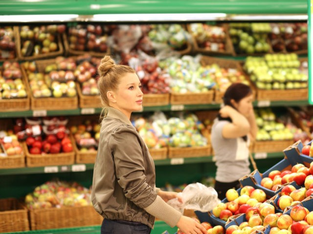 Middle-age woman buying vegetables at the market