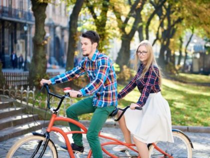 Young active happy traveler couple, handsome bearded man and pretty blond woman in glasses on tandem bike on bright sunny day on stony staircase and ancient building background.