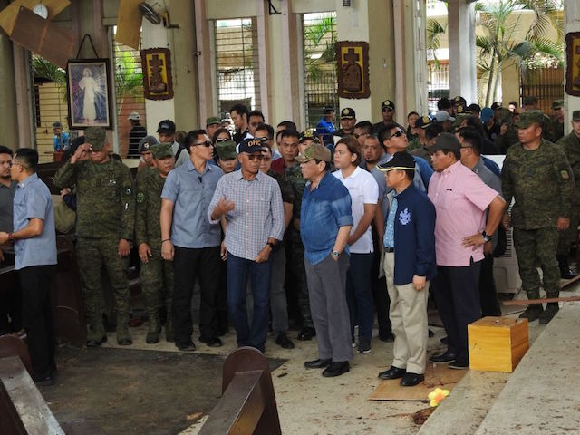 Philippine President Rodrigo Duterte (C, in blue shirt) accompanied by Defense Secretary Delfin Lorenzana (L, with spectacles) inspect the damage area of a catholic cathedral in Jolo town, sulu province, in southern island of Mindanao on January 28, 2019, a day after two explosions tore through the cathedral. - Investigators probing the Catholic cathedral bombing that killed 21 people in the Philippines' restive south said January 28, a group tied to notorious Islamists Abu Sayyaf is the prime suspect. (Photo by NICKEE BUTLANGAN / AFP) (Photo credit should read NICKEE BUTLANGAN/AFP via Getty Images)