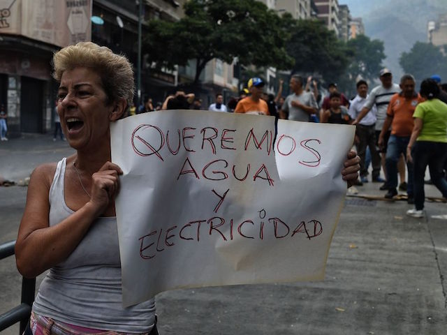 "TOPSHOT - A woman holds a placard reading ""We Want Water and Electricity"" as she shouts slogans during a protest for the lack of water and electric service during a new power outage in Venezuela, at Fuerzas Armadas Avenue in Caracas on March 31, 2019. - Living conditions are plummeting in the oil-producing Latin American nation, which is spiralling ever deeper into economic chaos during a protracted political crisis. (Photo by Federico PARRA / AFP) (Photo credit should read FEDERICO PARRA/AFP via Getty Images)"