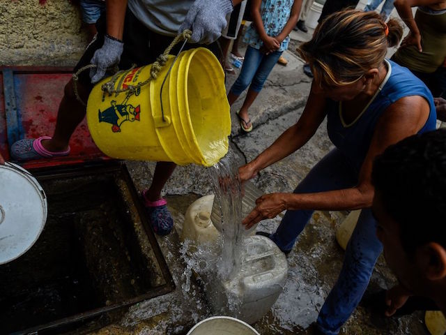 People draw water from a spring water tank to be used in their toilets, at Petare neighborhood in Caracas on April 1, 2019. - Venezuela's President Nicolas Maduro announced 30 days of electricity rationing Sunday, after his government said it was shortening the working day and keeping schools closed due to blackouts. (Photo by Federico Parra / AFP) (Photo credit should read FEDERICO PARRA/AFP via Getty Images)