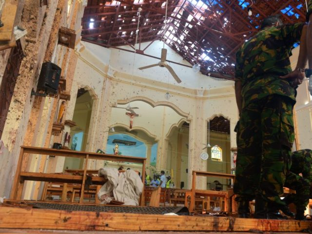 Security personnel inspect the interior of St. Sebastian's Church in Negombo on April 22, 2019, a day after the church was hit in series of bomb blasts targeting churches and luxury hotels in Sri Lanka. - The death toll from bomb blasts that ripped through churches and luxury hotels in …