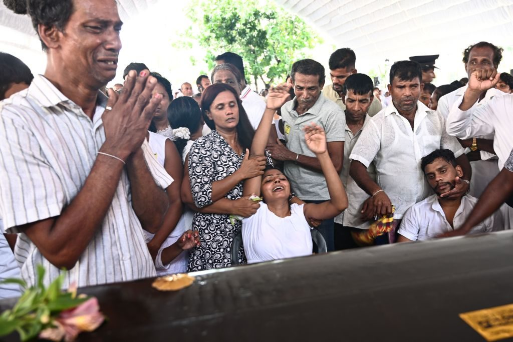 Relatives mourn beside a coffin of a bomb blast victim during a funeral service at St Sebastian's Church in Negombo on April 23, 2019, two days after a series of bomb attacks targeting churches and luxury hotels in Sri Lanka. - Sri Lanka began a day of national mourning on April 23 with three minutes of silence to honour nearly 300 people killed in suicide bomb blasts that have been blamed on a local Islamist group. (Photo by Jewel SAMAD / AFP) (Photo credit should read JEWEL SAMAD/AFP via Getty Images)