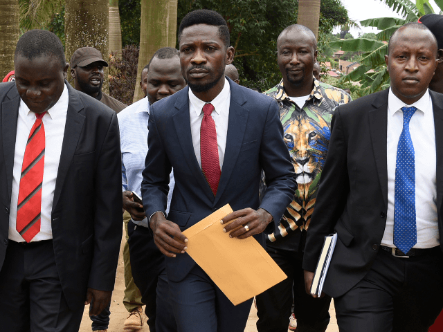 Ugandan musician turned politician, Robert Kyagulanyi, commonly known by his stage name Bobi Wine (C), is escorted by Uganda legislators after speaking to the press outside his home, in Kampala, on April 23, 2019. - Ugandan police detained Bobi Wine, on April 22, 2019 a pop star turned MP who …