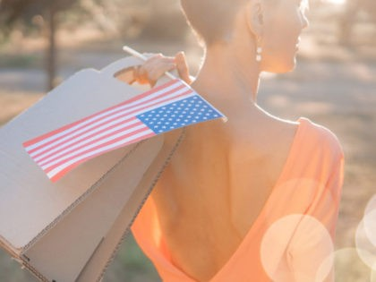 Young woman holding American flag and paper bag in spring park