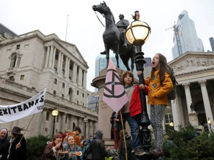 Activists protest outside the Bank of England (L) during the eighth day of demonstrations by the climate change action group Extinction Rebellion, in London, on October 14, 2019. (Photo by ISABEL INFANTES / AFP) (Photo by ISABEL INFANTES/AFP via Getty Images)