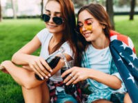 Two attractive young girls in sunglasses sitting in the Park on the lawn with the American flag, with a refreshing drink. U.S. independence day celebrations