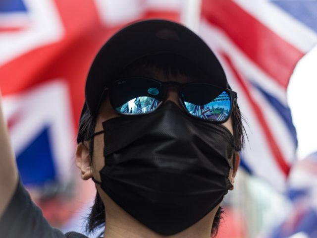 US and British Union Jack flags are seen reflected in a person's glasses as people take part in a pro-democracy march from Tsim Sha Tsui in the Kowloon district in Hong Kong on October 20, 2019. - Large crowds of Hong Kongers defied a police ban and began an illegal …
