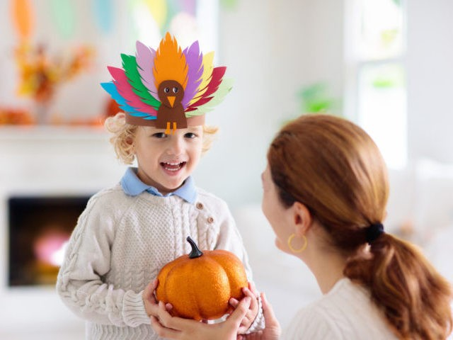 Child and mother celebrate Thanksgiving. Kid holding pumpkin in paper turkey hat. Autumn fun crafts and art. Mom and little boy in decorated living room. Warm knitted wear. Fall season decoration.