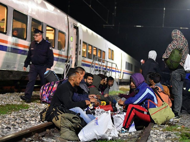 Bosnian police officer patrol outside the train as migrants from Asia and Africa rests after they arrives by train late in the night in Bosanska Otoka, Bosnia, on October 21, 2019. - No running water, putrid portable toilets and surrounding woods littered with land mines these are the bleak conditions …
