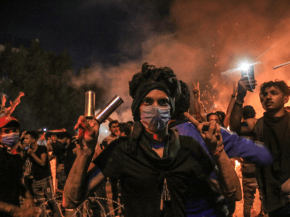 A protester wears tear gas canisters on his fingers and gestures the victory sign during anti-government protests in the Shiite shrine city of Karbala, south of Iraq's capital Baghdad, late on October 28, 2019. - Protests have persisted across Iraq and its Shiite-majority south, with night-time rallies in the central …