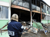 A Police officer stands in front of the burnt facade of the Tamaris elementary school in Beziers, southern France on November 1, 2019, after a fire of criminal origin destroyed several classrooms overnight. (Photo by SYLVAIN THOMAS / AFP) (Photo by SYLVAIN THOMAS/AFP via Getty Images)