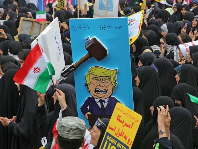 A picture taken on November 4, 2019, shows a placard mocking US president donald Trump during a rally outside the former US embassy in the Iranian capital Tehran on November 4, 2019, to mark the 40th anniversary of the Iran hostage crisis. - On November 4, 1979, less than nine …