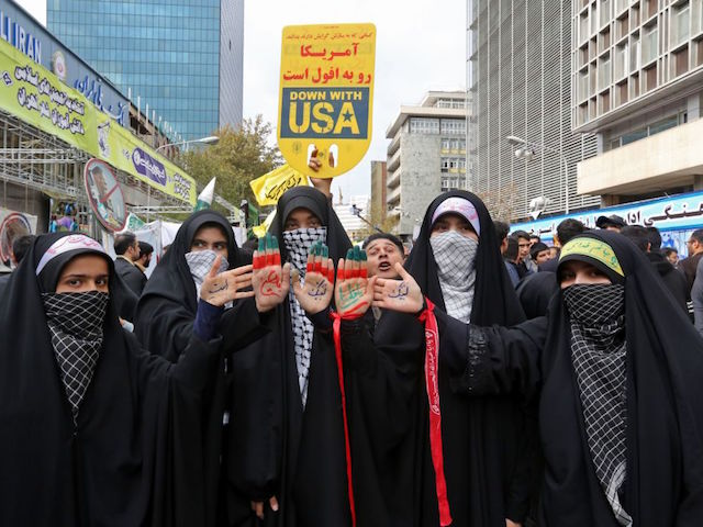 Iranian women display religious symbols written on the palms of their hands under a placard bearing anti-US slogans, during a demonstration outside the former US embassy in the Iranian capital Tehran on November 4, 2019, to mark the 40th anniversary of the Iran hostage crisis. - On November 4, 1979, less than nine months after the toppling of Iran's American-backed shah, students overran the embassy complex to demand the United States hand over the ousted ruler after he was admitted to a US hospital. (Photo by ATTA KENARE / AFP) (Photo by ATTA KENARE/AFP via Getty Images)