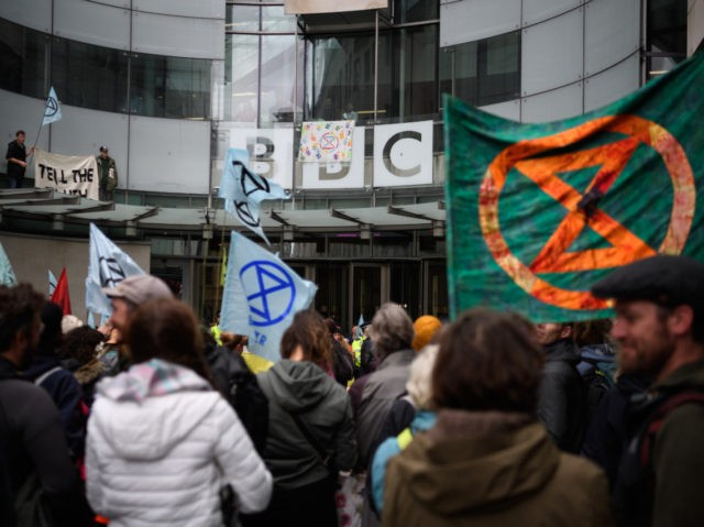 LONDON, ENGLAND - OCTOBER 11: Two men stand on a glass canopy above the entrance as Extinction Rebellion environmental campaigners gather outside the headquarters of the BBC to protest about their alleged silence over climate issues on October 11, 2019 in London, England. The Extinction Rebellion group is in the …