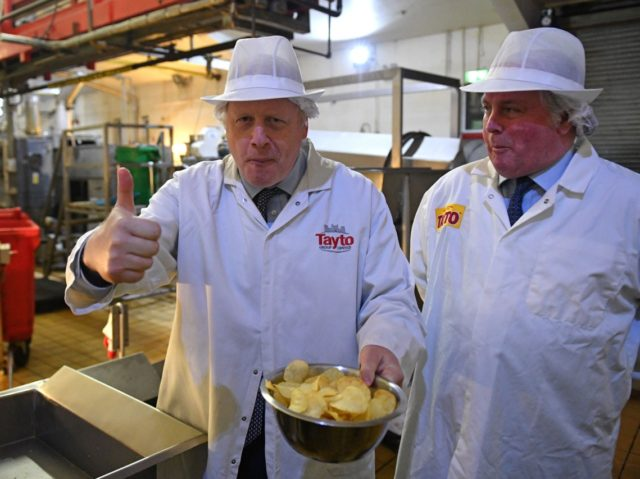 Britain's Prime Minister Boris Johnson (L) gestures besides Tayto Chairman Stephen Hutchinson (R) during a general election campaign visit to the Tayto Castle crisp factory in County Armagh, Northern Ireland, on November 7, 2019. - Britain's two main parties promised billions of pounds of investment for hospitals, schools and infrastructure …