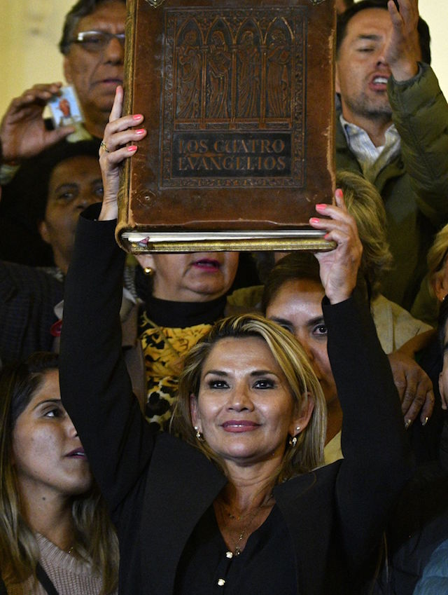 Deputy Senate speaker Jeanine Anez, raises the four canonical gospels in the air at the Quemado Palace in La Paz after proclaiming herself the country's new interim president in a session of Congress that failed to reach a quorum, on November 12, 2019. - Bolivia's Evo Morales jetted off to exile in Mexico on Tuesday, leaving behind a country in turmoil after his abrupt resignation as president. The country has been hit by weeks of unrest amid violent protests following Morales' contested re-election. (Photo by Aizar RALDES / AFP) (Photo by AIZAR RALDES/AFP via Getty Images)