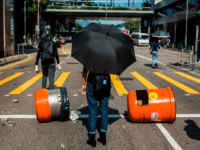 Pro-democracy protesters block a road during a demonstration in Central in Hong Kong on November 15, 2019. - Thousands of pro-democracy protesters took to Hong Kong's streets, defying a warning by Chinese President Xi Jinping, as a campaign of mass disruption extended into a fifth straight day. (Photo by ISAAC …