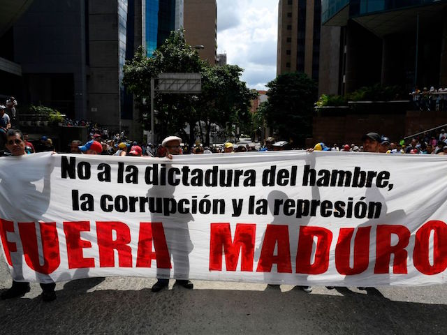 """Supporters of Venezuelan opposition leader and self-proclaimed acting president Juan Guaido hold a banner reading """"Maduro Out"""" as they take part in a demonstration against President Nicolas Maduro, in Caracas on November 16, 2019. - Venezuela's opposition called to protest against Maduro on Saturday, while the government also called on their own supporters to mobilize. (Photo by Federico PARRA / AFP) (Photo by FEDERICO PARRA/AFP via Getty Images)"""