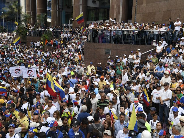 Supporters of Venezuelan opposition leader and self-proclaimed acting president Juan Guaido listen to his speech during a gathering in Caracas on November 16, 2019. - Venezuela's opposition called to protest against President Nicolas Maduroon Saturday, while the government also called on their own supporters to mobilize. (Photo by Federico PARRA / AFP) (Photo by FEDERICO PARRA/AFP via Getty Images)