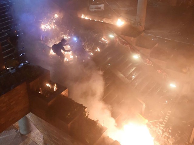 "TOPSHOT - Anti-government protesters start a large fire in a staircase at the main entrance that leads into the Hong Kong Polytechnic University in the Hung Hom district of Hong Kong on November 18, 2019. - Hong Kong police early November 18 warned for the first time that they may use ""live rounds"" after pro-democracy protesters fired arrows and threw petrol bombs at officers at a beseiged university campus, as the crisis engulfing the city veered deeper into danger. Protests have tremored through the global financial hub since June, with many in the city of 7.5 million people venting fury at eroding freedoms under Chinese rule. (Photo by Ye Aung Thu / AFP) (Photo by YE AUNG THU/AFP via Getty Images)"