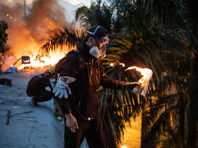 "HONG KONG, CHINA - NOVEMBER 18: A protester lights a petrol bomb in front of a fire on a pedestrian bridge during clashes with police at Hong Kong Polytechnic University on November 18, 2019 in Hong Kong, China. Anti-government protesters organized a general strike since Monday as demonstrations in Hong Kong stretched into its sixth month with demands for an independent inquiry into police brutality, the retraction of the word ""riot"" to describe the rallies, and genuine universal suffrage. (Photo by Laurel Chor/Getty Images)"