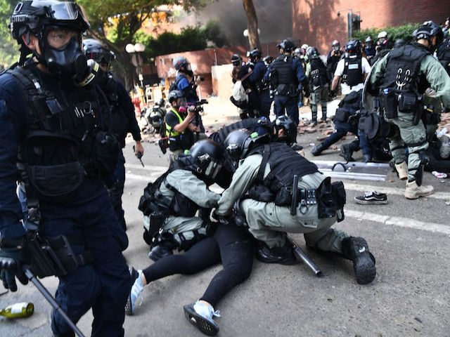 Protesters are detained by police near the Hong Kong Polytechnic University in Hung Hom district of Hong Kong on November 18, 2019. - Pro-democracy demonstrators holed up in a Hong Kong university campus set the main entrance ablaze on November 18 to prevent surrounding police moving in, after officers warned …