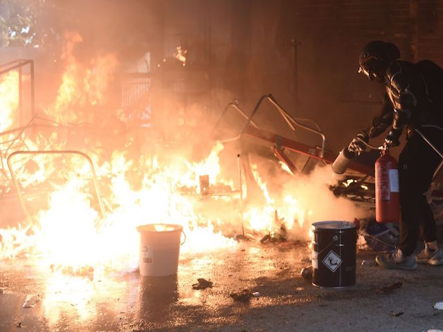 A student tries to extinguish a fire at the entrance of Hong Kong Polytechnic University in Hung Hom district of Hong Kong on November 18, 2019. - Pro-democracy demonstrators holed up in a Hong Kong university campus set the main entrance ablaze November 18 to prevent surrounding police moving in, after officers warned they may use live rounds if confronted by deadly weapons. (Photo by Ye Aung Thu / AFP) (Photo by YE AUNG THU/AFP via Getty Images)