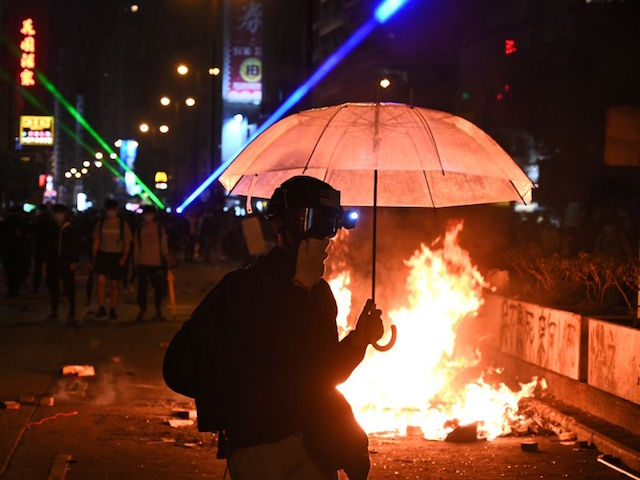 Protesters set a fire as they march to Hong Kong Polytechnic University in Hong Kong on November 18, 2019. - Pro-democracy demonstrators holed up in a Hong Kong university campus set the main entrance ablaze November 18 to prevent surrounding police moving in, after officers warned they may use live rounds if confronted by deadly weapons. (Photo by Philip FONG / AFP) (Photo by PHILIP FONG/AFP via Getty Images)