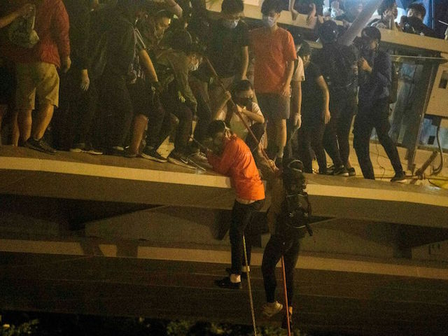 Protesters lower themselves down a rope from a bridge to a highway, to escape from Hong Kong Polytechnic University campus and from police, in Hung Hom district in Hong Kong on November 18, 2019. - Dozens of Hong Kong protesters escaped a two-day police siege at a campus late November 18 by shimmying down a rope from a bridge to awaiting motorbikes in a dramatic and perilous breakout that followed a renewed warning by Beijing of a possible intervention to end the crisis engulfing the city. (Photo by ANTHONY WALLACE / AFP) (Photo by ANTHONY WALLACE/AFP via Getty Images)
