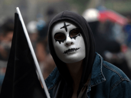 A demonstrator takes part in a protest against the government in Santiago on November 18, 2019. - President Sebastian Pinera condemned on Sunday for the first time what he called abuses committed by police in dealing with four weeks of violent unrest that have rocked Chile and which has left …