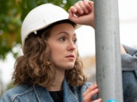 Close up portrait of a pensive and contemplative factory female employee wearing a white protective hard hat